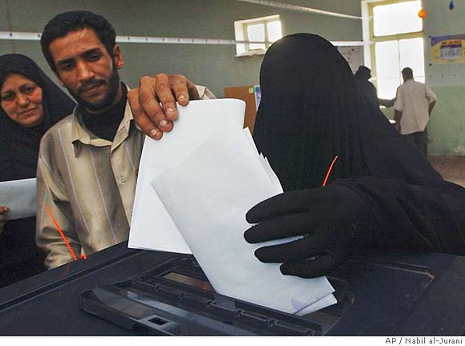 An Iraqi woman casts her vote at an election center in Basra, Iraq, Thursday, Dec. 15, 2005. Iraqis voted in a historic parliamentary election Thursday, with strong turnout reported in Sunni Arab areas and even a shortage of ballots in some precincts. Several explosions rocked Baghdad throughout the day, but the level of violence was low.(AP Photo/Nabil al-Jurani) Photo: NABIL AL-JURANI