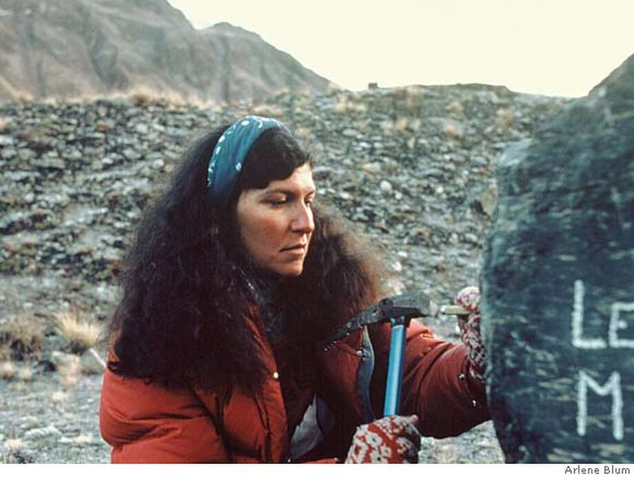 Arlene Blum soberly chisels the names of Vera Watson and Alison Chadwick-Onyszkiewicz into a boulder at base camp, two climbers who fell to their deaths during the otherwise successful campaign to put a women's team on the summit of Annapurna in 1978. Photo: Handout
