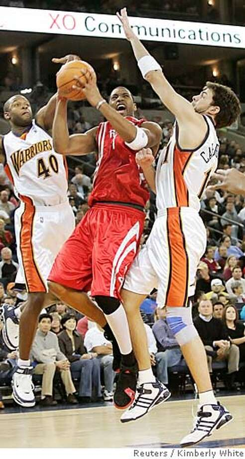 Houston Rockets Tracy McGrady (C) goes up for a shot against Golden State Warriors Calbert Cheaney (L) and Zarko Cabarkapa of Serbia Montenegro during a NBA basketball game in Oakland, California, December 14, 2005. REUTERS/Kimberly White 0 Photo: KIMBERLY WHITE