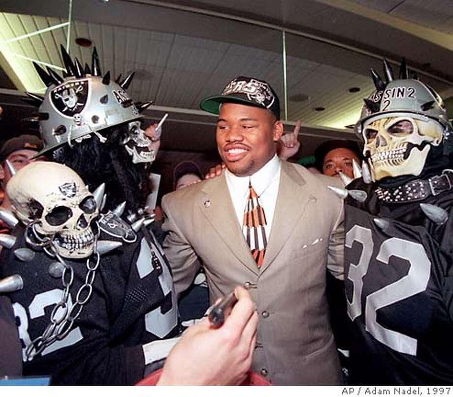 Darrell Russell, defensive tackle from Southern California, center, is surrounded by Oakland Raiders fans after being picked by the Raiders as their first-round pick in the NFL draft in New York, Saturday, April 19, 1997. (AP Photo/Adam Nadel) ALSO RAN 10/28/2003 Photo: ADAM NADEL