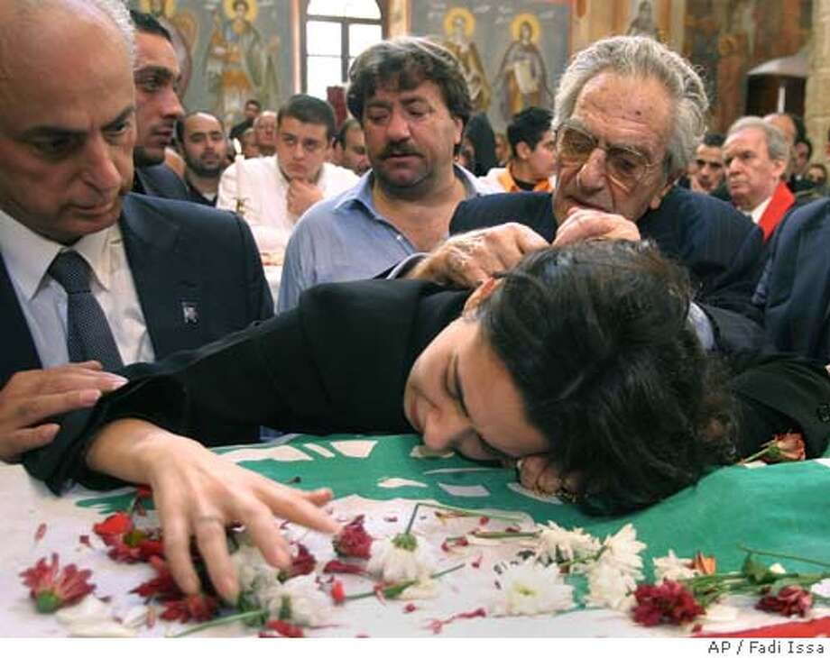 Nayla Tueni, foreground, daughter of slain anti-Syrian journalist and legislator Gibran Tueni, reacts over the coffin of her father, draped in a Lebanese flag, while she is comforted by her grandfather Ghassan Tueni, background right, and other relatives, during Tueni's funeral, in Beirut, Lebanon, Wednesday, Dec. 14, 2005. Tens of thousands of flag-waving Lebanese, both Christian and Muslim, poured into the streets Wednesday to bid farewell to anti-Syrian critic Tueni slain Monday in a car bombing, marching behind his coffin in a massive protest against the Syrian government many blame for his death. (AP Photo/Fadi Issa) Photo: FADI ISSA