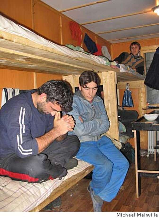 Farukh Montzarov, 26, (left) and Said Haitov, 25 (right), inside the steel storage container where they live with six others on a construction site in northern Moscow. Both are illegal migrant workers from southern Tajikistan. Photo by Michael Mainville Photo: Michael Mainville