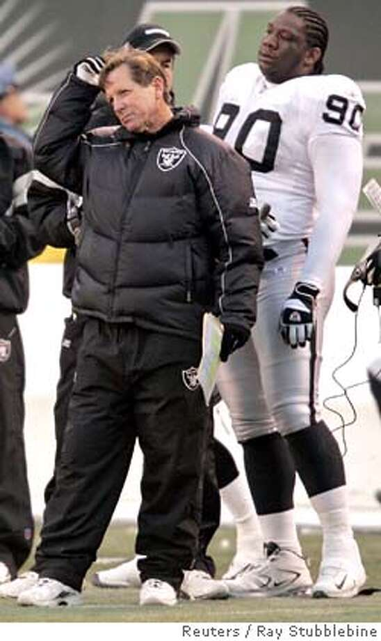 Oakland Raiders coach Norv Turner (L) and tackle Terdell Sands (90) watch the end of the game in their 26-10 loss to the New York Jets in their NFL game in East Rutherford, New Jersey, December 11, 2005. REUTERS/Ray Stubblebine 0 Photo: RAY STUBBLEBINE