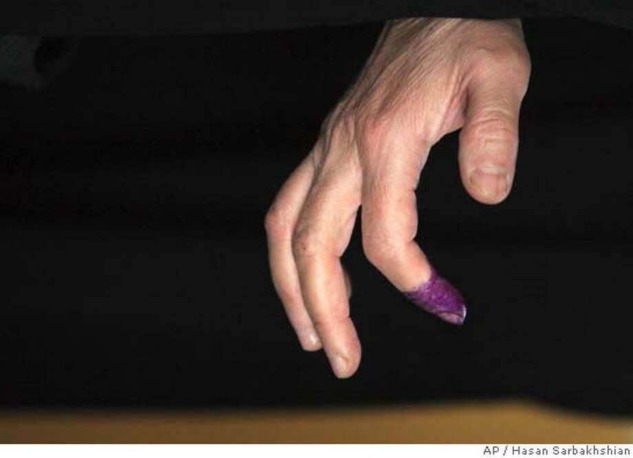 The hand of an Iraqi woman with her right index finger covered with purple ink to show she has voted during Iraqi parliamentary elections, at a polling station in Tehran, Iran, Wednesday, Dec. 14, 2005. Iraqi expatriates are permitted to cast absentee ballots in 15 countries across the world, in the country's parliament elections.(AP Photo/Hasan Sarbakhshian) Photo: HASAN SARBAKHSHIAN