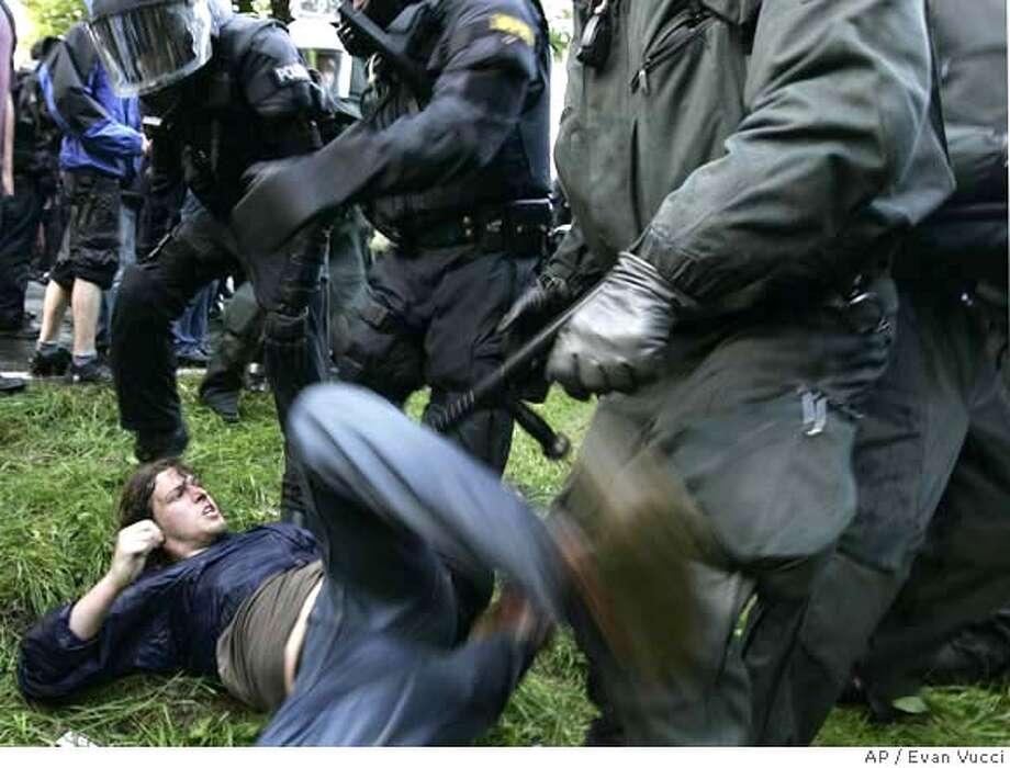 A Protester is thrown to the ground during a clash with German police as they block a main access road to the G8 meetings in Hinter Bollhagen, Germany, Wednesday, June 6, 2007. (AP Photo/Evan Vucci) Photo: Evan Vucci