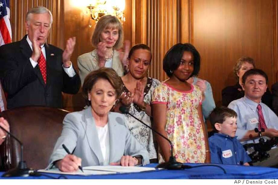 House Speaker Nancy Pelosi of Calif., seated, signs a stem cell research bill on Capitol Hill in Washington, Thursday, June 7, 2007. House Majority Leader Steny Hoyer of Md., standing, left, Rep. Lois Capps, D-Calif., standing, second from left, and others, look on. (AP Photo/Dennis Cook) Photo: Dennis Cook