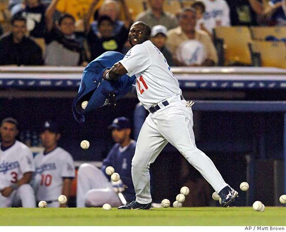 Los Angeles Dodgers' Milton Bradley throws a bag of baseballs onto the field after being ejected from the game by umpire Terry Craft for arguing balls and strikes against the Milwaukee Brewers in the sixth inning Tuesday, June 1, 2004, at Dodgers Stadium in Los Angeles. (AP Photo/Matt Brown) Photo: MATT BROWN