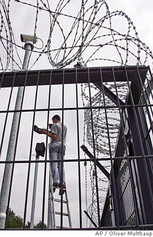 A technician adjusts security cameras at the high security fence built around the G8 summit site of Heiligendamm, Germany, Sunday, June 3, 2007. The G-8 summit will take place there from Wednesday, June 6, 2007 to Friday, June 8, 2007. (AP Photo/Oliver Multhaup) Photo: Oliver Multhaup