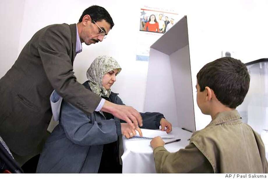 ** CORRECTS DATE TO DEC. 13 ** Adel Tuwarish, left, helps his wife, Wassan, center, vote in Iraq's national election as their son, Ali, 6, watches in Pleasanton, Calif., Tuesday, Dec. 13, 2005. Iraqi expatriates across the United States cast absentee ballots Tuesday in their homeland's historic parliamentary elections, hoping to pick leaders who can curb seemingly uncontrollable violence and allow many to visit home _ in some cases for the first time in decades. (AP Photo/Paul Sakuma) Photo: PAUL SAKUMA