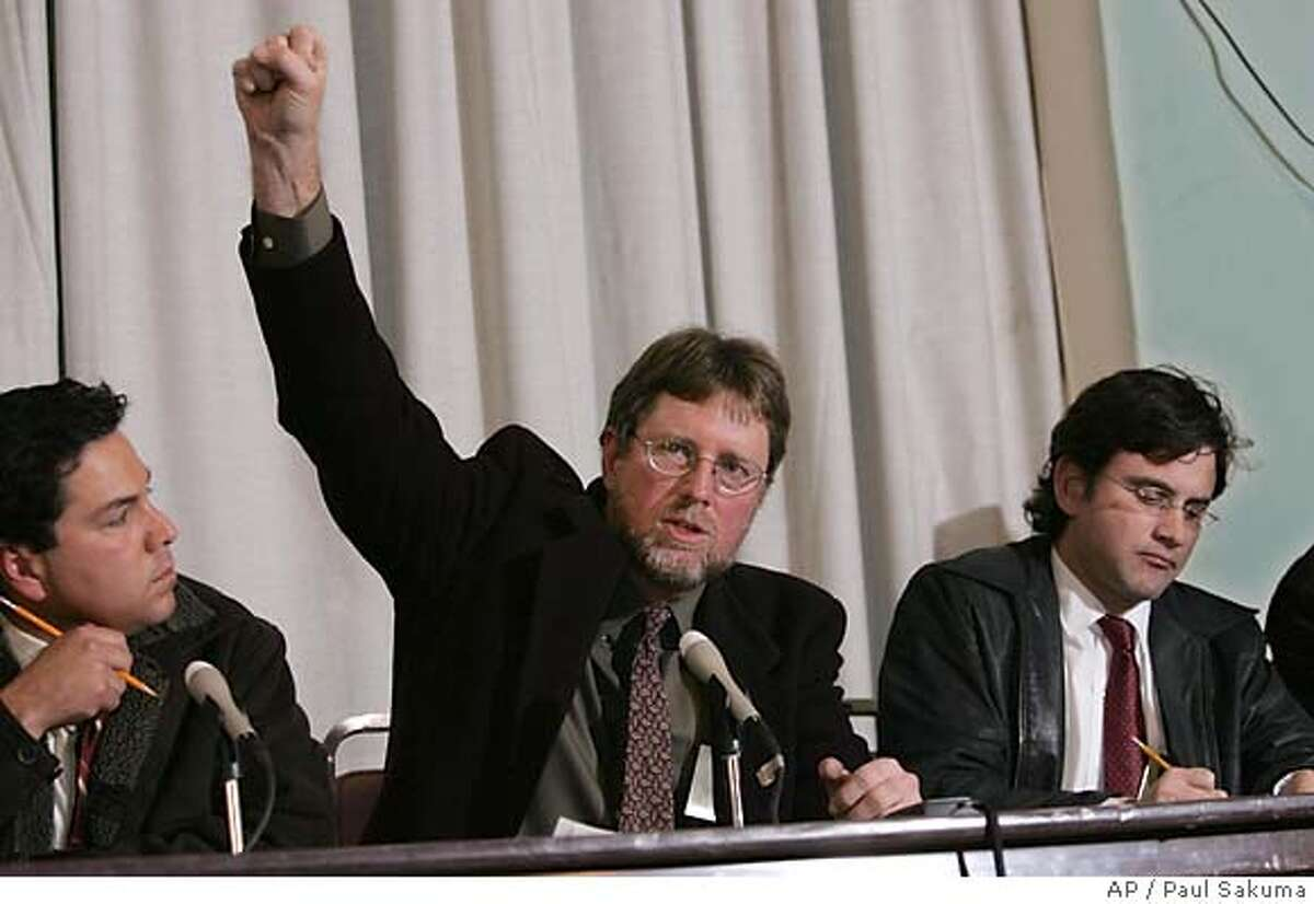 San Francisco Chronicle reporter Kevin Fagan, who witnessed the execution of Stanley Tookie Williams, gestures at a news conference in San Quentin State Prison in San Quentin, Calif., Tuesday, Dec. 13, 2005. Williams, 51, died by injection just after midnight for murdering four people during two 1979 holdups. The gesture referred to how supporters of Williams gestured after the executiion. At left is UPN reporter Tony Lopez and right is Contra Costa Times reporter John Simerman. (AP Photo/Paul Sakuma)