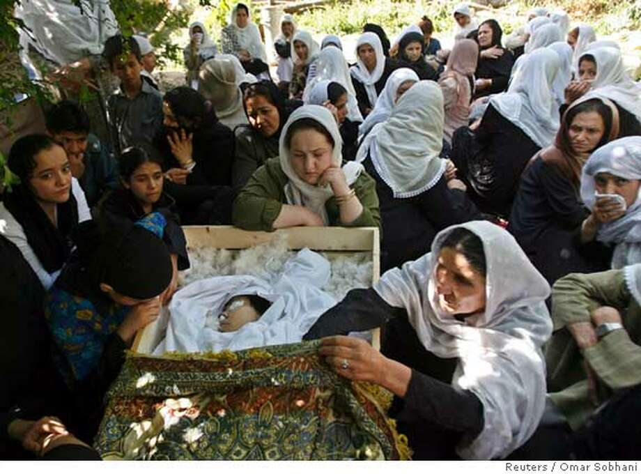 Relatives of slain Afghan journalist Zakia Zaki, 35, mourn her death at her funeral in Parwan province June 6, 2007. Zaki was shot by unidentified gunmen after she refused demands by militants to shut down her Western-funded radio station. REUTERS/Omar Sobhani (AFGHANISTAN)  Ran on: 06-07-2007  Relatives of slain Afghan journalist Zakia Zaki mourn at her funeral in Parwan province. She refused to shut her radio station. Photo: STRINGER/AFGHANISTAN