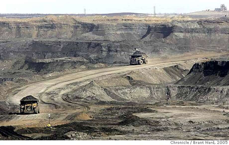 "ft_mcmurray751_ward.jpg  At the Chevron oilsands project north of Fort McMurray, giant earth haulers drive into the canyon created by the strip mining process. They work 24 hours a day carrying the raw dirt coated with oilsands out of the manmade canyon. The oil sands area of Alberta, Canada is perhaps the answer to  Canada and America's energy needs for the next 40 years. The oil is attached to tiny grains of sand and dirt and is being mined all around the city of Fort McMurray.  This has caused a ""boomtown"" atmosphere in the small town. Even with good salaries for workers at the oil sands, rents and home prices rival Northern California. Many of the ""homeless"" make over $30,000 a year, but still can't afford the high rents. The young workers go a little crazy on weekends at the local casino and bars...the famous mounties must patrol outside.  This is a portrait of the oil sands and the town that is paying the price. Brant Ward 4/20/05 Ran on: 05-22-2005  Refining oil sands is so difficult and expensive because the oil must be extracted from sand and clay. But with oil prices on the rise, mining Canada's vast reserves has become profitable. Ran on: 05-22-2005  Refining oil sands is difficult and expensive because the oil must be extracted from sand and clay. But with oil prices on the rise, mining Canada's vast reserves has become profitable. Ran on: 05-22-2005 Photo: Brant Ward"