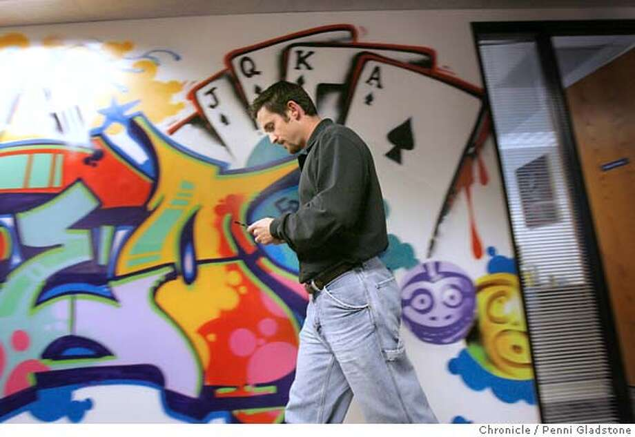 STARTUP05_0083_PG.JPG Justin Kubiak looks at his cell phone as he walks by a wall of graffite in the office  Glu Mobile. The Bay Area is once again at the heart of a new technological industry, this time its mobile content for cell phones, you know stuff like games, ring tones, searches. The Bay area has become the premier hub for mobile startups, in part because we have the technological know how here and because of the entreprenurial spirit in the Bay. Photo taken by Penni Gladstone/The San Francisco Chronicle  Photo taken on 12/1/05, in San Mateo, CA. MANDATORY CREDIT FOR PHOTOG AND SF CHRONICLE/ -MAGS OUT Photo: Penni Gladstone