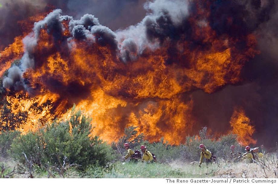 ** CORRECTS NAME OF FIRE ** A crew of Hotshots pulls back as a section of the Larson Fire rages, a result of high winds and dry conditions in Coleville, Calif., Tuesday, June 5, 2007. Winds gusting up to 65 mph fanned a Sierra wildfire that forced the evacuation Tuesday of up to 200 people near the California-Nevada line and the closure of a 40-mile stretch of U.S. Highway 395. (AP Photo/The Reno Gazette-Journal, Patrick Cummings) Photo: Patrick Cummings