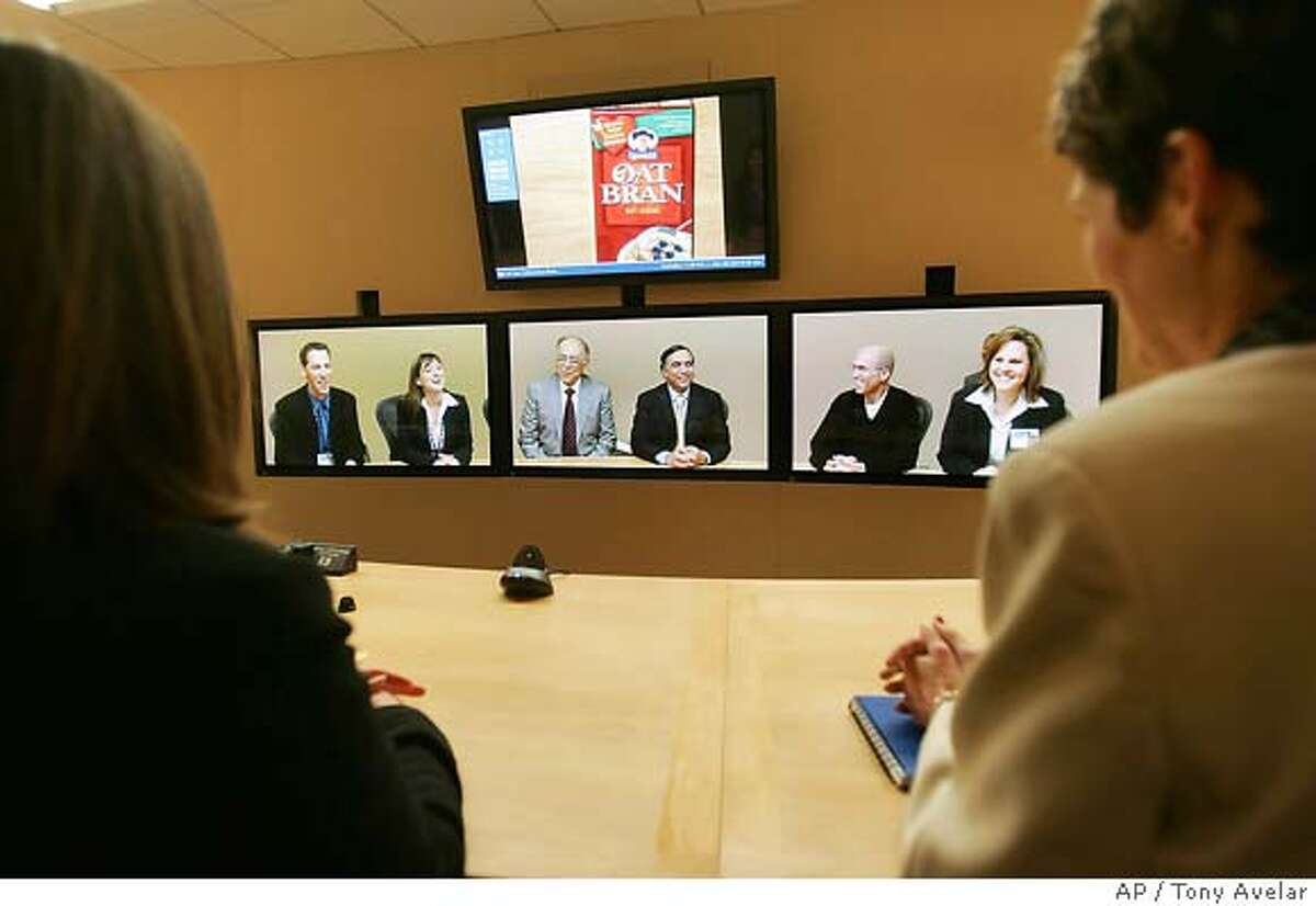"""Porter Novelli employees Eric Allen and Lisa Peterson; Advanced Micro Devices Inc. Chairman and CEO Hector Ruiz and Hewlett-Packard executive vice president, of Imaging & Printing Group, Vyomesh """"VJ"""" Joshi; Jeffrey Katzenberg, CEO of DreamWorks Animation and Alyson Griffin from HP, appear together on monitors from left, during a virtual conference with Hewlett- Packard employees in Palo Alto, Calif., Monday, Dec. 12, 2005. HP in partnership with DreamWorks Animation introduced a first-of-its-kind Halo Collaboration Studio that enables people in different locations to communicate in a vivid, face-to-face environment in real time. (AP Photo/Tony Avelar)"""