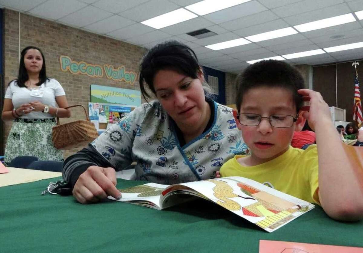 Valerie Elizondo and son Aiden Elizondo, 6, read a book as teacher Marivel Garcia watches during the
