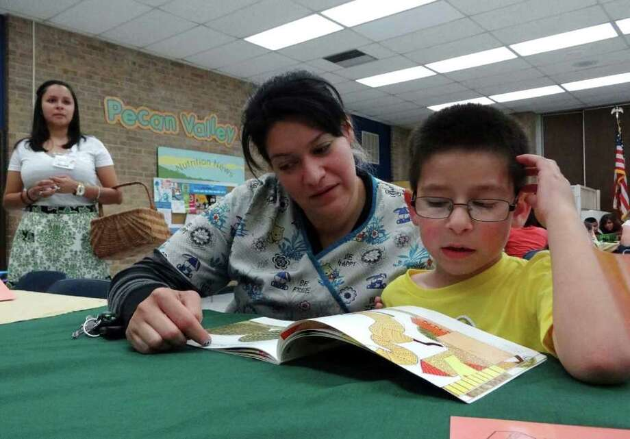 """Valerie Elizondo and son Aiden Elizondo, 6, read a book as teacher Marivel Garcia watches during the """"Reading Restaurant"""" event at Pecan Valley Elementary School on Thursday, March 8, 2012. Children were served by their teachers, who played the part of waiters and waitresses, but instead of taking orders for food, they took orders for books. Photo: Billy Calzada, San Antonio Express-News / San Antonio Express-News"""