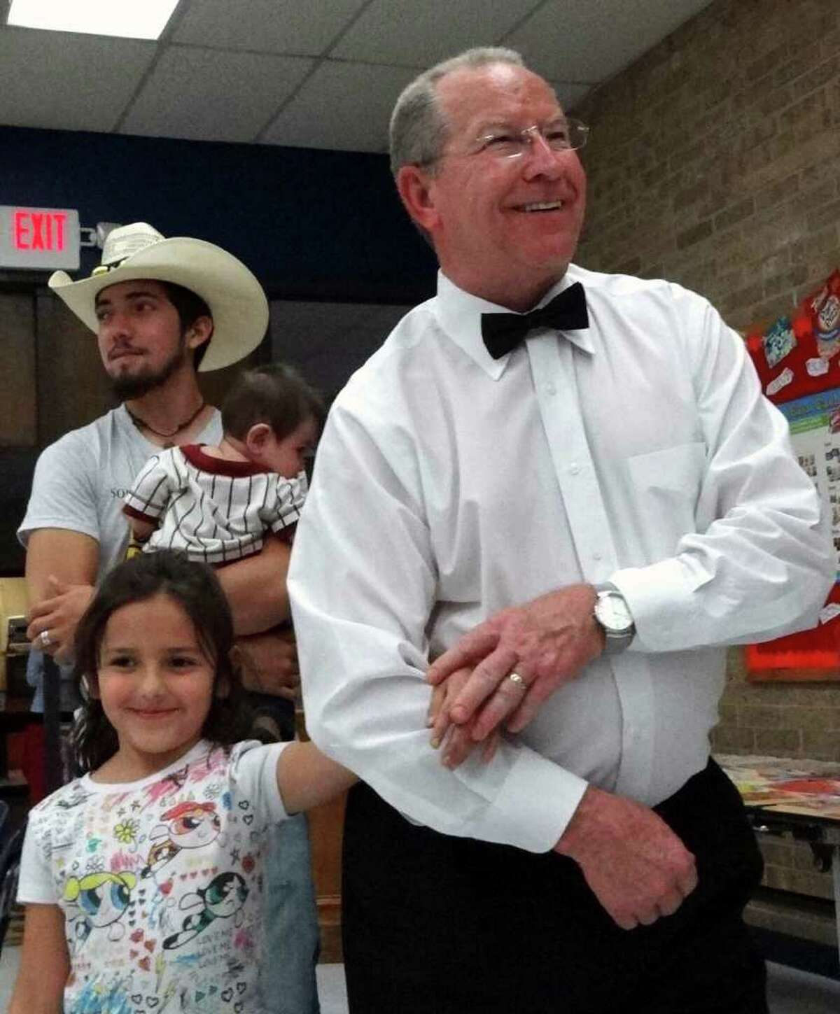 Merrill Ramsey, principal of Pecan Valley Elementary School, escorts Joey Edenfield, 7, to her chair during the