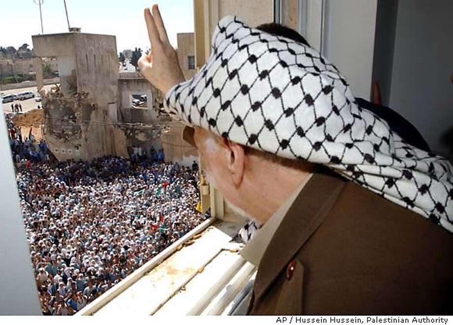 In this photo made available from the Palestinian Authority, Palestinian leader Yasser , peers out of his headquarters' window to flash the V-sign as he salutes hundreds of schoolchildren gathered to support him outside his headquarters in the West Bank town of Ramallah, Saturday Sept. 13, 2003. Ten years after the signing of historic peace accords whose goals were never achieved, Yasser said Saturday the Mideast conflict is facing its most difficult point since and he urged Israel to return to negotiations following its threat to exile him. (AP Photo/Palestinian Authority, Hussein Hussein, HO) ** ** Photo: HUSSEIN HUSSEIN