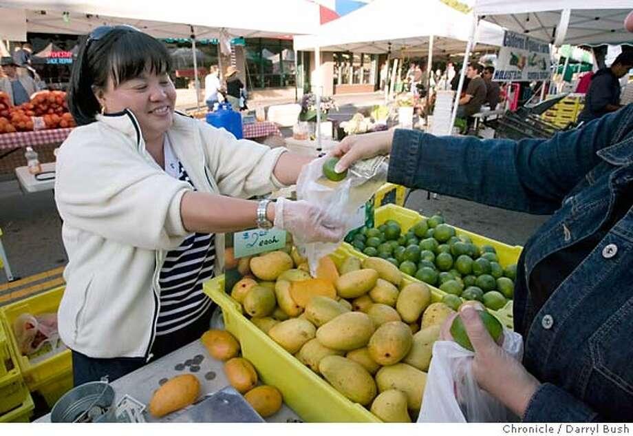 farmmarket20_sancarlos_0015_db.JPG  Andrea Tran of Family Farm Fruits of Palmdale, CA., left, sells fresh mangos and limes at the San Carlos Farmer's Market in San Carlos, CA, on Thursday, May, 31, 2007. photo taken: 5/31/07  Darryl Bush / The Chronicle ** Andrea Tran (cq) MANDATORY CREDIT FOR PHOTOG AND SF CHRONICLE/NO SALES-MAGS OUT Photo: Darryl Bush