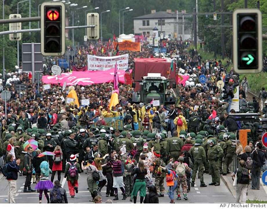 German police officers and demonstrators walk together during a demonstration in Rostock, northeastern Germany, Monday, June 4, 2007, a couple of days ahead of the upcoming G8 summit in Heiligendamm. (AP Photo/Michael Probst) Photo: MICHAEL PROBST
