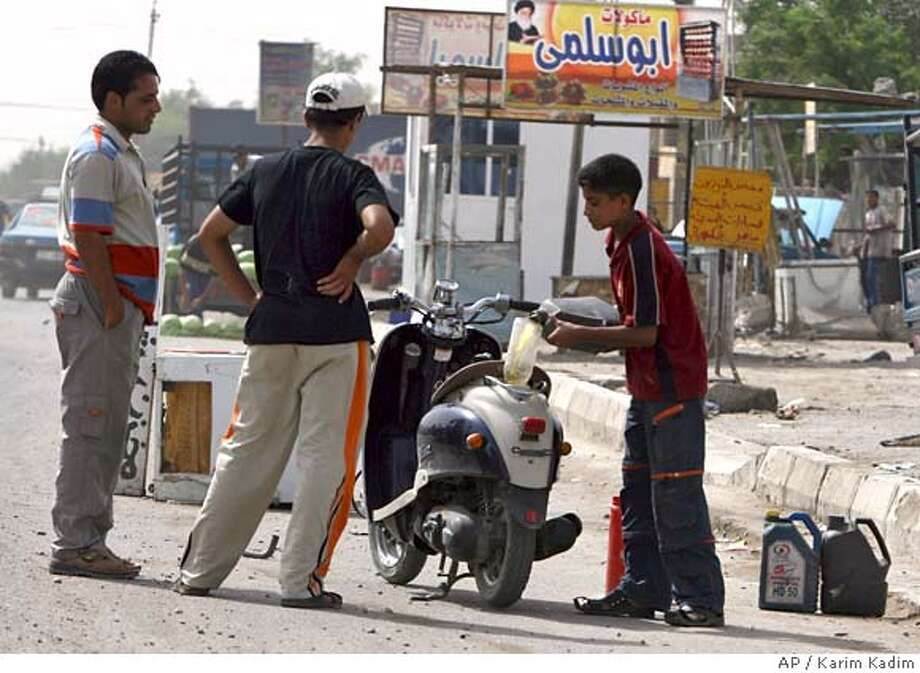 A young Iraqi boy fills up the gasoline tank of a motorcycle in Baghdad, on Sunday, June 3, 2007. Gasoline on the black market _ sold by kids by the curbside waving plastic containers _ costs about US$1 per liter,the cost of a liter gasoline in a gas station is about 25 US cents, but people have to wait more than eight hours to fill their gasoline tank and instead prefer to pay more. (AP Photo / Karim Kadim) Photo: KARIM KADIM