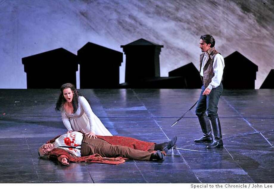 "OPERA_05_02_JOHNLEE.JPG  Donna Anna, left, played by Elza van den Heever (cq), mourns over the death of her father, the Commendatore, played by Kristinn Sigmundsson (cq), during the first act of Saturday night's perfomance of the San Francisco Opera's ""Don Giovanni."" Donna Ottavio, played by Charles Castronovo (cq), at right.  By JOHN LEE/SPECIAL TO THE CHRONICLE Photo: JOHN LEE"