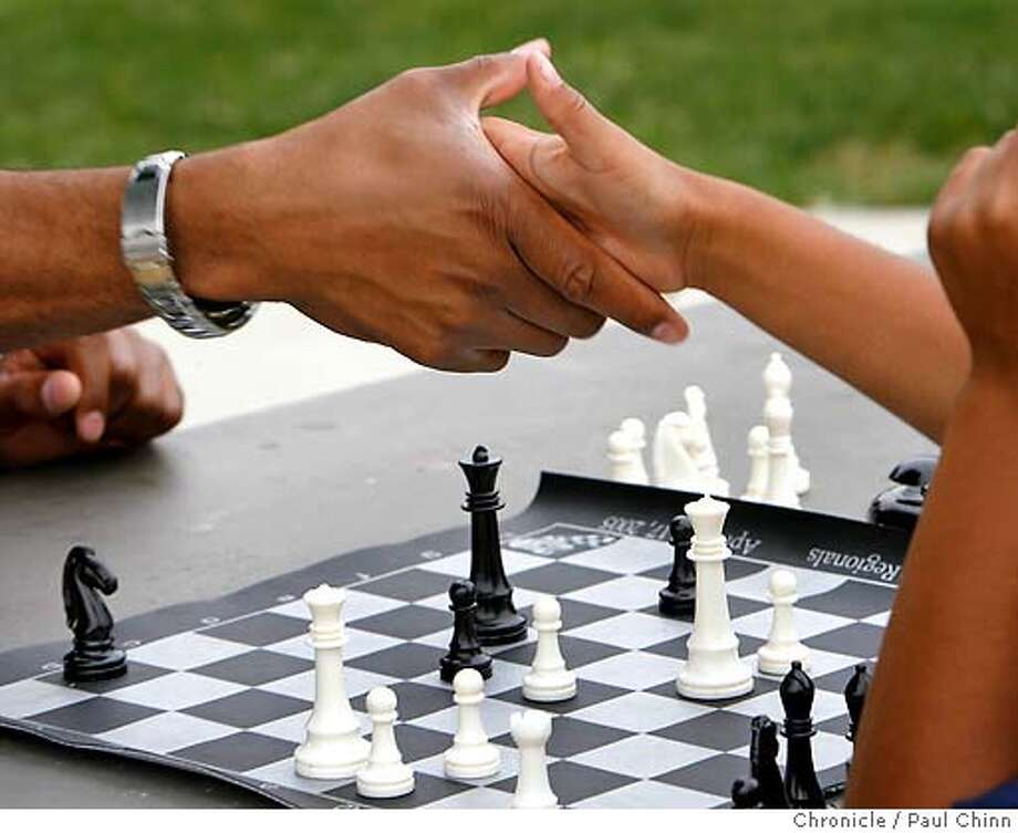 Adisa Banjoko, co-founder of the Hip Hop Chess Federation, and his eight-year-old son Ayinde shake hands after a game of chess at a neighborhood park in Fremont, Calif. on Saturday, May 26, 2007. PAUL CHINN/The Chronicle  **Adisa Banjoko, Ayinde MANDATORY CREDIT FOR PHOTOGRAPHER AND S.F. CHRONICLE/NO SALES - MAGS OUT Photo: PAUL CHINN