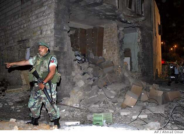 A Lebanese soldier stands guard next to a damaged house after a bomb exploded next to an empty passenger bus, east of Beirut, Lebanon, Monday June 4, 2007. A bomb exploded in an empty passenger bus parked in a Christian neighborhood east of Beirut Monday, injuring 10 passers-by, a senior security official reported. Lebanon has seen a string of bomb explosions in and around Beirut since clashes between Fatah Islam militants and the Lebanese army began May 20.(AP Photo/Ahmad Omar) Photo: AHMAD OMAR