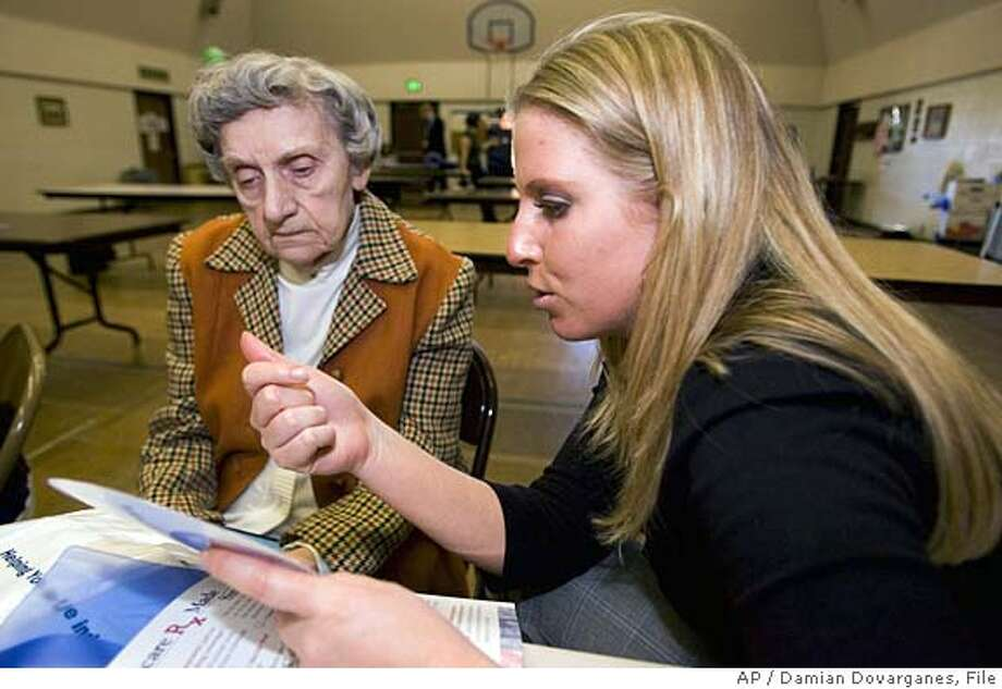 Mary Spring, 83, from Los Angeles, is briefed on Medicare prescription drug benefits program by Jillian Green, an advocacy group field organizer with Medicare Today, during a seniors Medicare drug workshop, Thursday, Nov. 17, 2005, at the Van Nuys-Sherman Oaks Senior Center in Sherman Oaks, Calif. (AP Photo/Damian Dovarganes) NOV 17 2005 PHOTO Photo: DAMIAN DOVARGANES