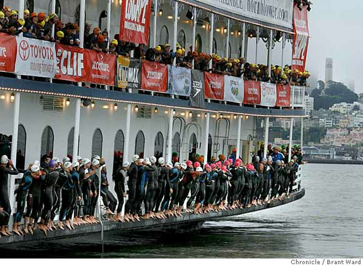 Athletes lined the sides of a ferry boat in preparation for the start of the triathlon. In background is San Francisco's Coit Tower. Hundreds of triathlon athletes got an early start to the Accenture Escape from Alcatraz Triathlon Sunday beginning with a 1.5 mile swim from a boat near Alcatraz to the San Francisco shoreline. Then an 18 mile bike ride and an eight mile run. {Brant Ward/San Francisco Chronicle}6/3/07
