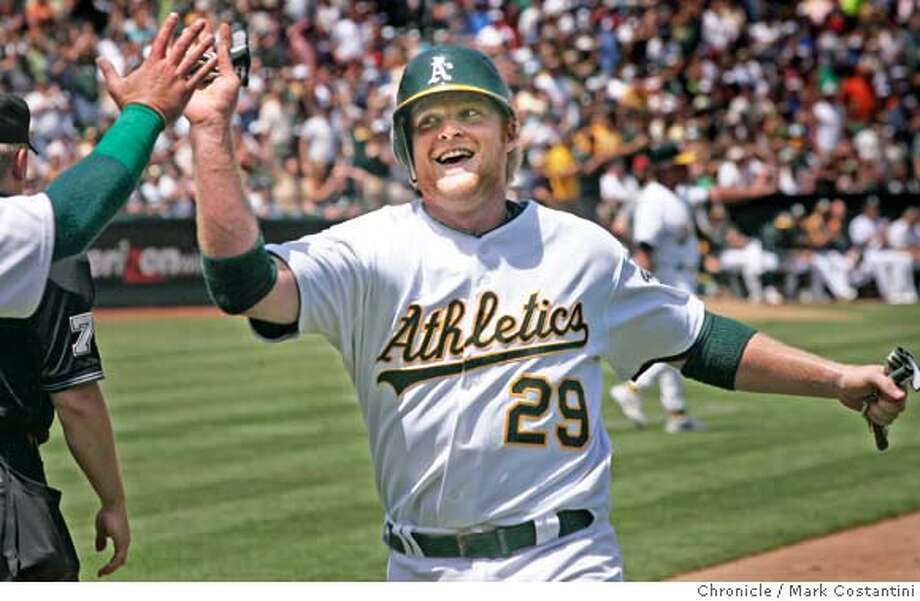 A's Baseerunner Dan Johnson smiles as scores a rn and gets a high five in the 3rd inning.  A's beat the Twins at the Coliseum  PHOTO: Mark Costantini / The Chronicle Photo: MARK COSTANTINI