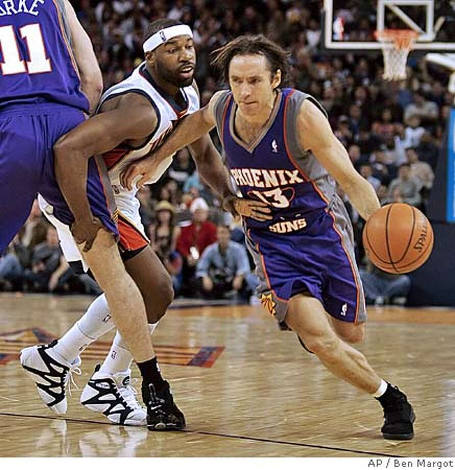 Phoenix Suns' Steve Nash (13) drives around Golden State Warriors' Baron Davis, who is blocked by Suns' Pat Burke in the first half, Wednesday, Dec. 7, 2005, in Oakland, Calif. (AP Photo/Ben Margot) Photo: BEN MARGOT