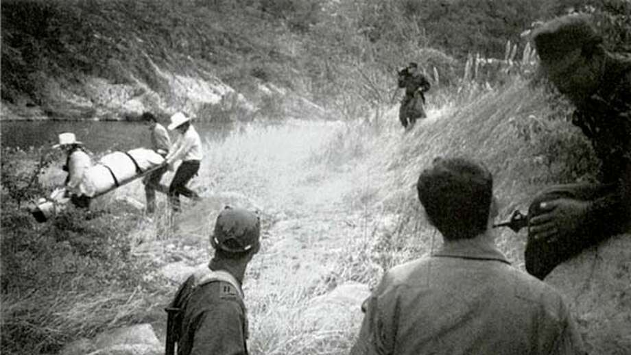 "A Mexican forensics team carries Philip True's body out of the Twisted Serpent Canyon in Mexico's Sierra Madre, as Mexican soldiers look on. Photo from ""Trail of Feathers''"