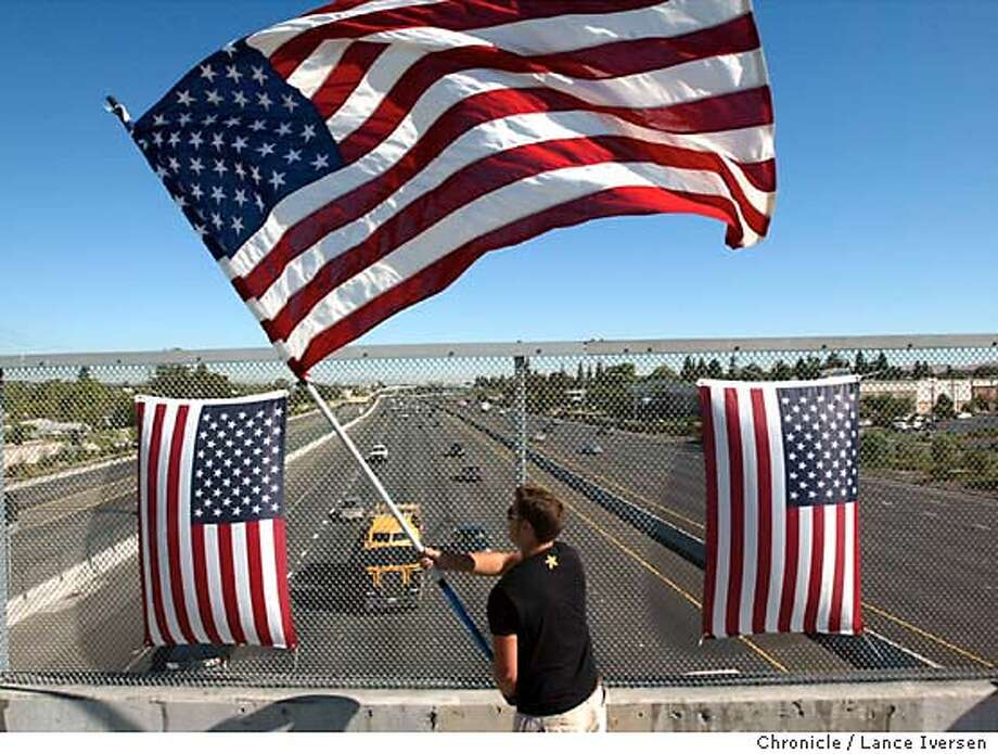 911FLAGS0129LI.jpg  Remembering the World Trade Center attacks, Joey David from Plesant Hill stands on the Pleasant Hill Blvd overpass on highway 680 waving the American flag to passing south bound motorists thursday morning. Photo by LANCE IVERSEN, The San Francisco Chronicle Photo: LANCE IVERSEN