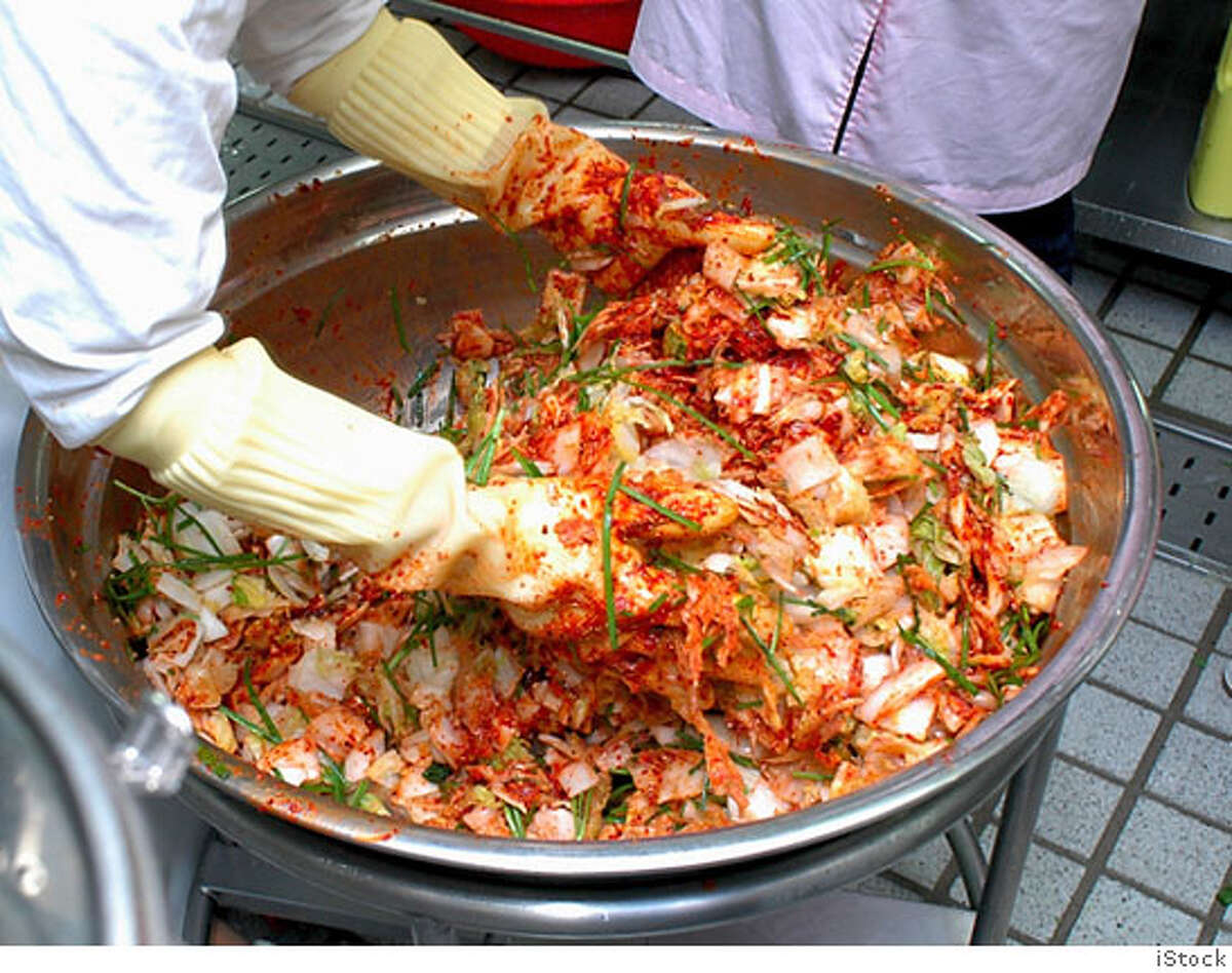 hand-mixing Kimchi ingredients (spicy cabbage side-dish photo credit iStock
