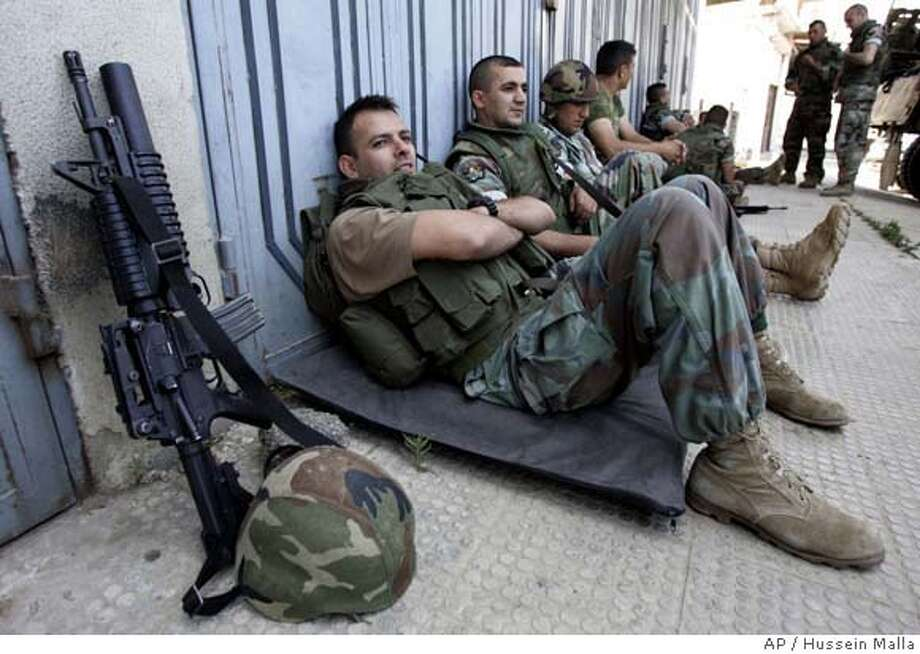 Lebanese army soldiers from navy commandos units, sit on the ground as they wait to replace another unit in the Palestinian refugee camp of Nahr el-Bared during clashes with fighters from the Fatah Islam militant group, in the northern city of Tripoli, Saturday June 2, 2007. Lebanon's army suffered more casualties as it pressed ahead with an offensive to uproot al-Qaida-inspired militants, pounding their hideouts in a Palestinian refugee camp with artillery a day after sending tanks and armored vehicles to seize positions in the camp's outer neighborhoods.(AP Photo/Hussein Malla) Photo: HUSSEIN MALLA