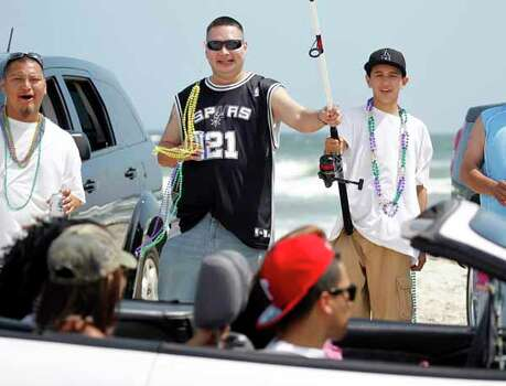 Alex Lopez, left, Julian Ramirez, center, and Frankie Gonzalez, 15, dangle a fishing pole with beads in front of passing cars driving across the beach Friday, March 16, 2012 during spring break near Padre Island in Corpus Christi, Texas. (AP Photo/Corpus Christi Caller-Times, Michael Zamora) MANDATORY CREDIT; MAGS OUT; TV OUT Photo: Michael Zamora, Associated Press / AP2012