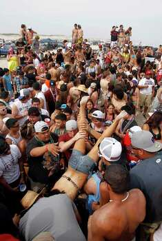 A crowd of beach goers take turn doing keg stands Thursday March 15, 2012 as they celebrate spring break near Padre Island in Corpus Christi, Texas. (AP Photo/Corpus Christi Caller-Times, Michael Zamora) TV OUT, MAGS OUT; MANDATORY CREDIT Photo: Michael Zamora, Associated Press / AP2012