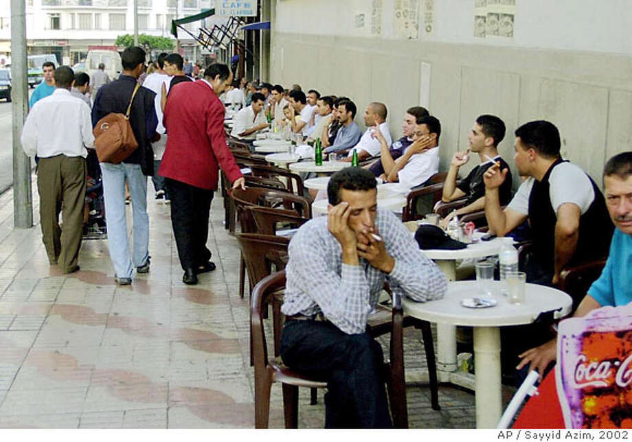 Young men drink sodas, coffee and mint tea Aug. 13, 2002, at an outdoor cafe on Tangier's boulevard Pasteur. Despite a construction boom in the northern Moroccan city, unemployment is high, and young men spend a lot of time in cafes.(AP Photo/Sayyid Azim) Photo: SAYYID AZIM