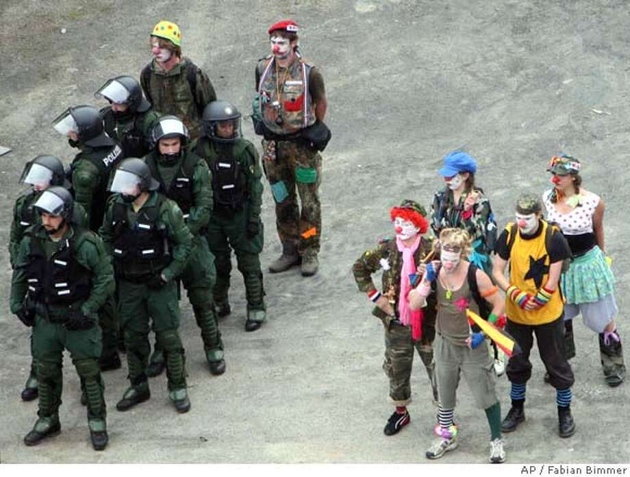 Protesters, dressed as clowns, stand beside German riot police as they take part in a demostration against the upcoming G8 summit in Rostock, Germany, on Saturday, June 2, 2007. Several thousands people demonstrated against the G8 summit, which will start on Wednesday, June 6 in Heiligendamm at the Baltic Sea. Dozens of different groups, including communists, anarchists and environmentalists, were taking part and messages were mixed: Some urged action from the G-8 countries in the fight against HIV/AIDS, African poverty and climate change, while others questioned the legitimacy of the existence of the G-8 itself. The protest comes ahead of the three-day summit that opens Wednesday in the nearby northern resort town of Heiligendamm, where German Chancellor Angela Merkel hosts the leaders of the other G-8 nations _ Britain, France, Japan, Italy, Russia, Canada, and the United States. (AP Photo/Fabian Bimmer) Photo: FABIAN BIMMER