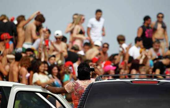 A driver stands on her car seat to get a photo of the spring break action Thursday March 15, 2012 on the beach near Padre Island in Corpus Christ, Texas. (AP Photo/Corpus Christi Caller-Times, Michael Zamora) MANDATORY CREDIT; MAGS OUT; TV OUT Photo: Michael Zamora, Associated Press / AP2012