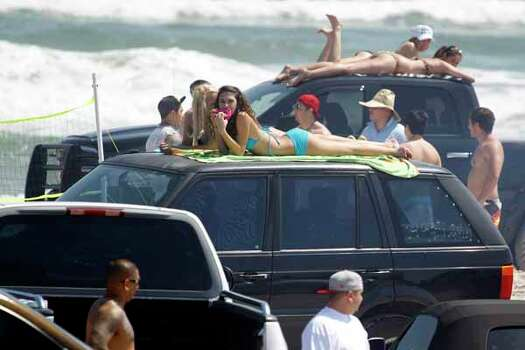 Spring breakers sun bathe on top of their vehicles as they watch the crowds walk by Wednesday, March 14, 2012 as they spend spring break at J.P. Luby Park in Corpus Christi, Texas. (AP Photo/Corpus Christi Caller-Times, Michael Zamora) MANDATORY CREDIT; MAGS OUT; TV OUT Photo: Michael Zamora, Associated Press / AP2012