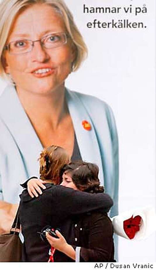 Two woman embrace in front of billboard featuring Swedish Foreign Minister Anna in downtown Stockholm Thursday Sept. 11, 2003. died Thursday after she was stabbed multiple times in an upscale Stockholm department store by an unknown assailant Wednesday. (AP Photo/Dusan Vranic) Photo: DUSAN VRANIC