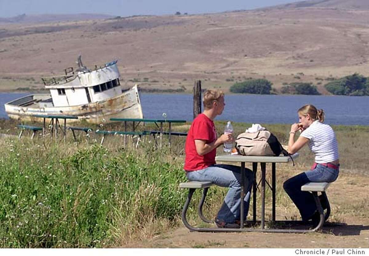 Thomas Diefenbach and Judith Ehrke, tourists from Germany, enjoy a picnic lunch in front of a beached fishing boat in Inverness. Tomales Bay on 9/3/03.