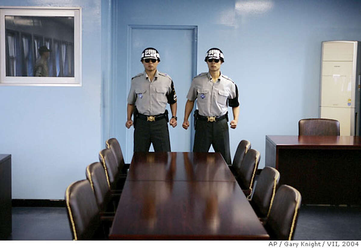 South Korean Military Police stand guard in the military armistice meeting room, where all official contact between the militaries of North Korea, South Korea and the United States takes place at the truce village of Panmunjom in the demilitarized zone that separates the two Koreas. Each South Korean soldier is a Black belt in Tae Kwon Do, is taller than average, wears sunglasses, so the North Koreans can't see their eyes, and has been security cleared. (AP Photo/Mandatory Credit/Gary Knight/VII)
