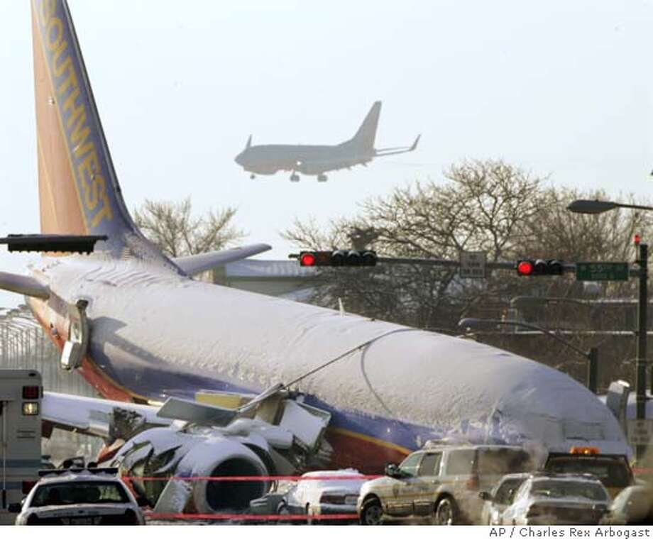 A Southwest Airlines Boeing 737, background, lands at Chicago's Midway Airport over the wreckage of another Southwest Airlines 737 as it rests nose first in the intersection of W. 55th Street and Central Ave. after it skidded off the runway and through a barrier fence Thursday night in Chicago, Friday, Dec. 9, 2005. Flight 1248 from Baltimore to Chicago tried to land in heavy snow sliding off a runway crashing through the boundary fence and crushing one car killing one. (AP Photo/Charles Rex Arbogast) Ran on: 12-10-2005  A Southwest Airlines 737 rests on a city street, a day after skidding off a snowy runway at Chicago's Midway Airport. Photo: CHARLES REX ARBOGAST