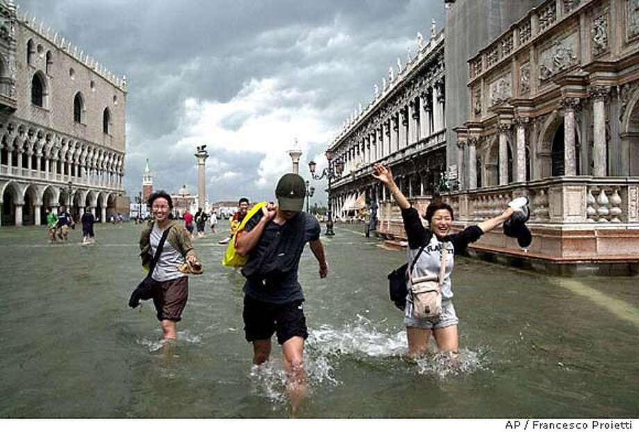 Tourists play in high water in St. Mark's square in , Italy, Thursday, June 6, 2002. Italian meteorologists said that the high water level is a record for June. The water reached the 125-centimeter mark (49 inches), and experts say it could go as high as 130 centimeters (51 inches). (AP Photo/Francesco Proietti) Photo: FRANCESCO PROIETTI