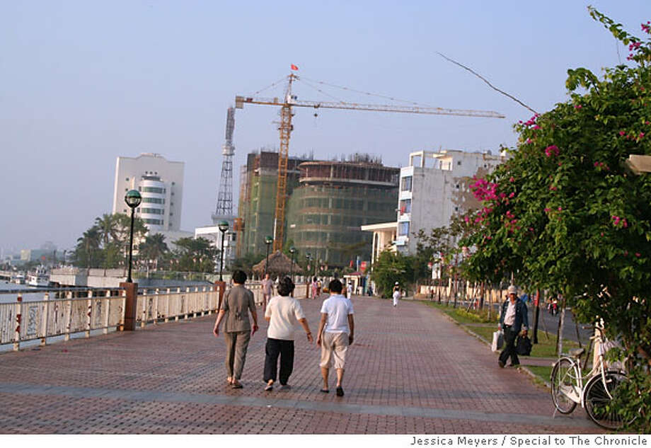 Cranes and half-constructed buildings are a common sight for strollers who walk Danang's promenade along the Han River. Ran on: 06-03-2007  Construction cranes and new buildings are a common sight for strollers along Danang's promenade on the Han River. Photo: Jessica Meyers
