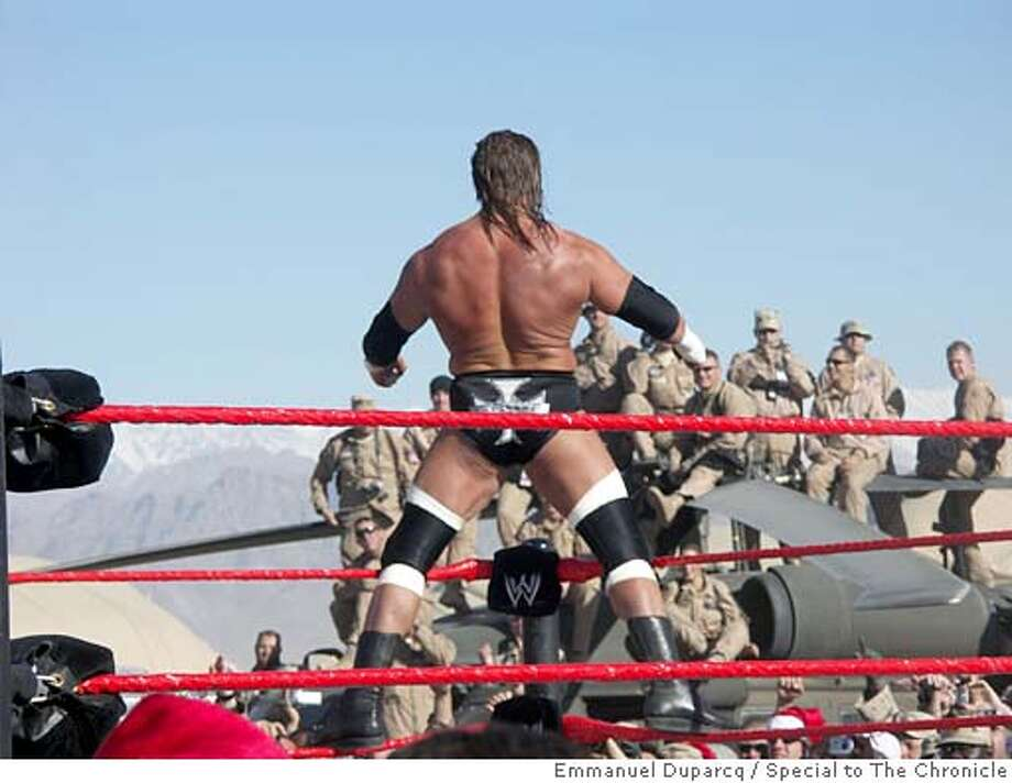 American troops watch as Wrestler Triple H flexes his muscles fbefore a match. Photo by Emmanuel Duparcq/Special to The Chronicle Ran on: 12-10-2005  Wrestler Triple H flexes his muscles as U.S. troops check out his pre-match warm-up routine. Photo: Emmanuel Duparcq